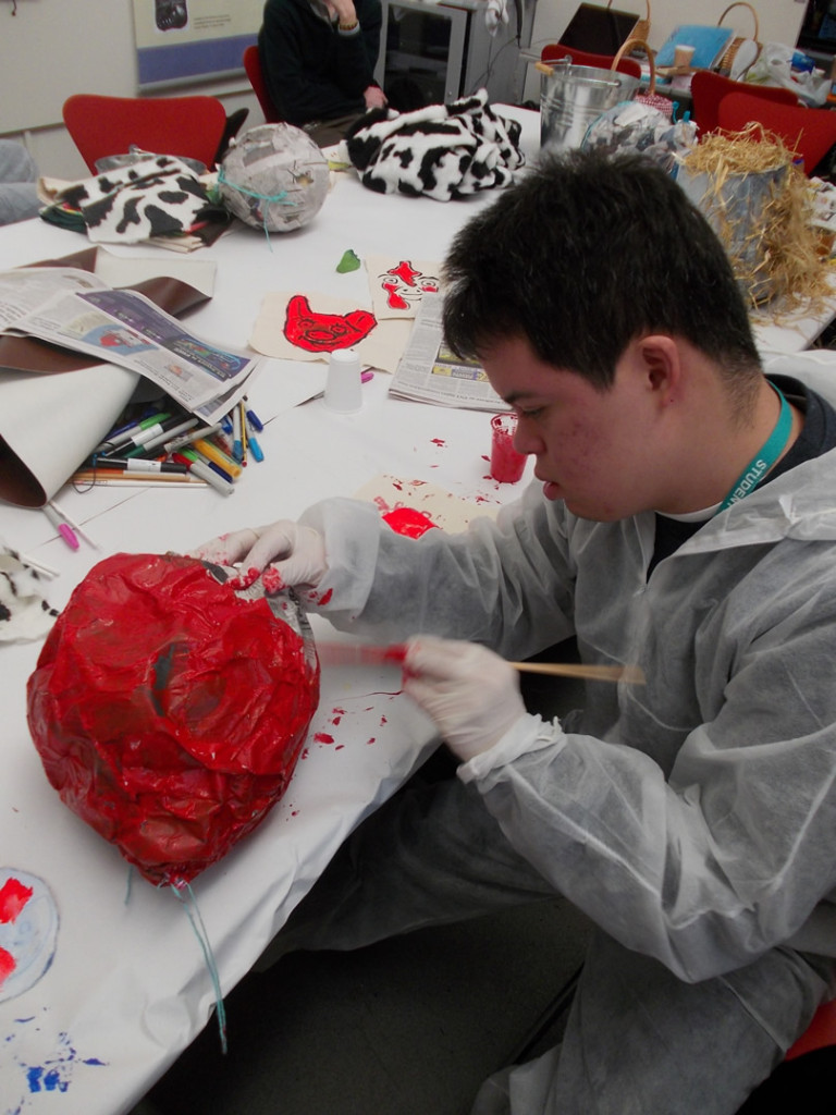Guillermo paint his papier mache in bright red.